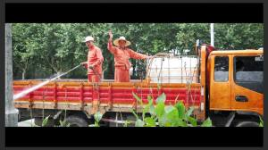 Happy workers spraying deadly pesticides on bushes and pedestrians alike
