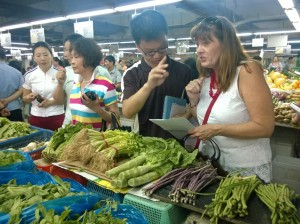 Patti working with Dodo, our guide, to buy ingredients at the wet market